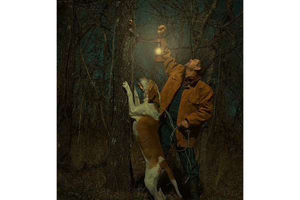 man with dog and lantern looking up into tree
