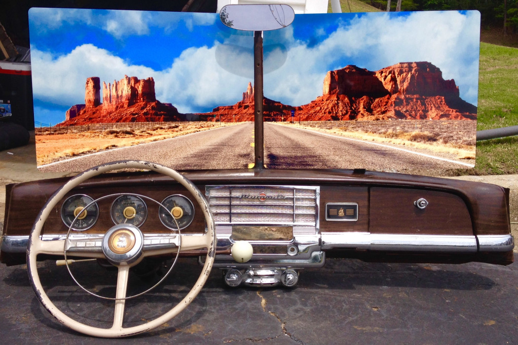 2 metal prints balanced on the dashboard of an old plymouth