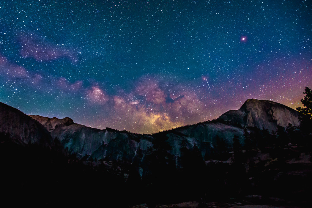 photo of the milky way over a mountain range in the night sky