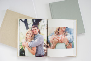open photo book stacked on top of 2 closed photo books