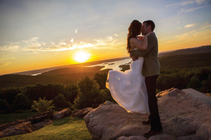 a couple standing on a rock kissing at sunset
