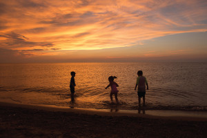 3 children frolick on a beach at sunset